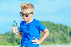 Portrait of a thirsty handsome boy in sunglasses drinking water. On the desert tropical beach Royalty Free Stock Photography