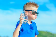 Portrait of a thirsty handsome boy in sunglasses drinking water. On the desert tropical beach Stock Photos