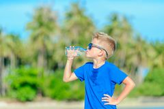 Portrait of a thirsty handsome boy in sunglasses drinking water. On the desert tropical beach Stock Photography