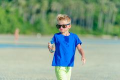 Portrait of a thirsty handsome boy in sunglasses drinking water. On the desert tropical beach Stock Images