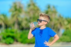 Portrait of a thirsty handsome boy in sunglasses drinking water. On the desert tropical beach Royalty Free Stock Photo