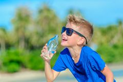 Portrait of a thirsty handsome boy in sunglasses drinking water. On the desert tropical beach Stock Image