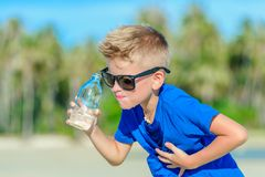 Portrait of a thirsty handsome boy in sunglasses drinking water. On the desert tropical beach Stock Photo