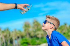 Portrait of a thirsty handsome boy in sunglasses drinking water. On the desert tropical beach Royalty Free Stock Images