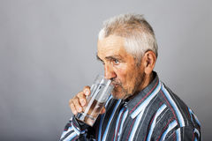 Portrait of a  thirsty senior man drinking water. Isolated over gray background Stock Image