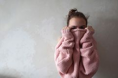Teenage girl in pink knitted sweater. Portrait of thirteen year old girl hiding her face in warm pink knitted loose sweater. Photo with copy space on background royalty free stock images
