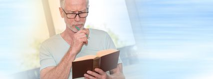 Portrait of thoghtful mature man reading a book, light effect Royalty Free Stock Photos