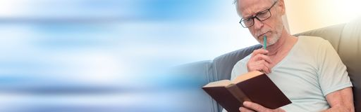 Portrait of thoghtful mature man reading a book, light effect Stock Photography
