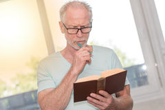 Portrait of thoghtful mature man reading a book, light effect Royalty Free Stock Images