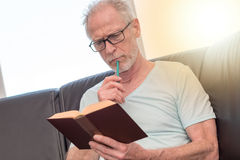 Portrait of thoghtful mature man reading a book, light effect Royalty Free Stock Photography