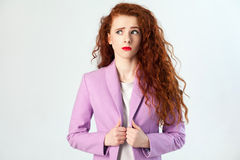 Portrait of thoughtful beautiful business woman with red - brown hair and makeup in pink suit. thinking and looking away Royalty Free Stock Photo