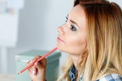 Portrait of thoughtful beautiful female designer holding pencil Stock Image