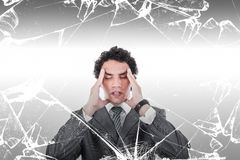 Portrait of thoughtful business man with headache behind broken stock image