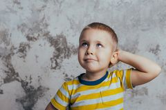 Portrait of a thoughtful cute little child with hand touching face stock photo