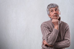 A portrait of thoughtful dreamy senior man standing over white background with copy space for your advertisement.  Mature man deep Royalty Free Stock Photos