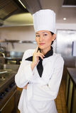 Portrait of thoughtful female cook in kitchen Stock Images