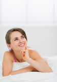 Portrait of thoughtful girl laying on bed. In living room Stock Image