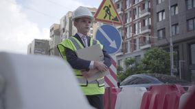 Portrait thoughtful little boy wearing safety equipment and constructor helmet holding building plan standing on a busy stock video