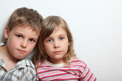 Portrait of thoughtful little girl and boy. They put heads on each other Stock Image