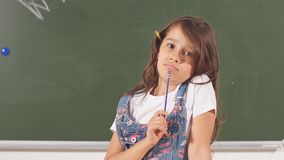 Portrait of thoughtful little smiling girl holding pencil. Genius child with the idea
