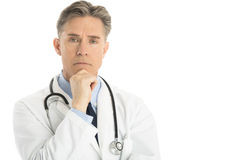 Portrait Of Thoughtful Male Doctor With Hand On Chin. Standing against white background Stock Photos