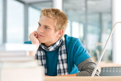 Portrait of thoughtful male student with books. Portrait of male student with books looking at camera sitting at table Royalty Free Stock Image