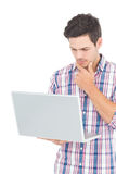 Portrait of thoughtful male student using a laptop. On white background Royalty Free Stock Photos
