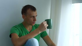 Portrait of thoughtful man drinking cup of tea stock video footage