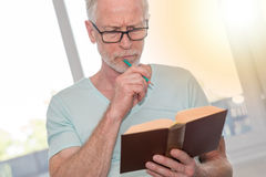 Portrait of thoughtful mature man reading a book, light effect Royalty Free Stock Image