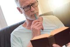 Portrait of thoughtful mature man reading a book, light effect Royalty Free Stock Photo