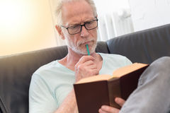 Portrait of thoughtful mature man reading a book, light effect Royalty Free Stock Images