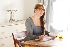 Thoughtful mature woman writing in a book in morning. Portrait of thoughtful mature woman sitting at a table with pen and book at home in morning Royalty Free Stock Photo