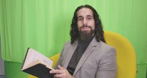 Portrait of thoughtful Middle Eastern man sitting with book on yellow armchair. Young male writer in formal suit looking