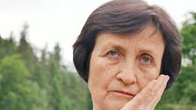 Portrait of thoughtful sad senior woman with short dark hair and wrinkles on her face on mountain hill with green forest