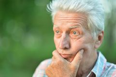 Portrait of thoughtful senior man. With hand on chin   in  park Royalty Free Stock Image