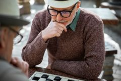 Mature male pensioner thinking about next move in checkers Royalty Free Stock Photos