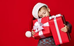 Portrait of thoughtful boy in Santa hat isolated on red background stock photo