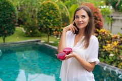 Portrait thoughtful girl holds dragon fruits in her hand, thinks of eating or not eating it royalty free stock images