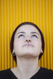 Portrait of a thoughtful teen gay woman with a piercing on her n. Ose isolated on yellow background Royalty Free Stock Photography