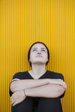 Portrait of a thoughtful teen lesbian woman on a yellow wall Stock Image