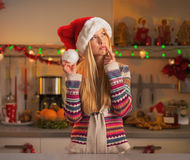 Portrait of thoughtful teenage girl in santa hat in kitchen Stock Photography