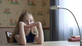Portrait thoughtful teenager girl sitting at table in home office. Face pensive teenager girl thinking at work table in stock video