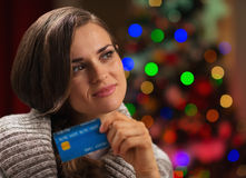 Portrait of thoughtful woman with credit card Stock Image