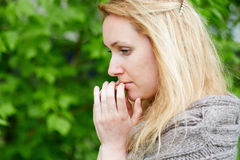 Portrait of thoughtful woman in hand-knitted jacket Stock Photo