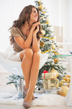 Portrait of thoughtful woman sitting in front of christmas tree. Full length portrait of thoughtful young woman sitting in front of christmas tree Stock Photos