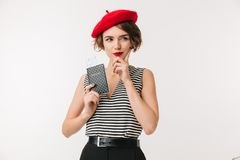 Portrait of a thoughtful woman. Wearing red beret holding passport isolated over white background Stock Photos