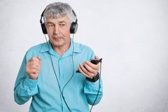 Portrait of thoughtful wrinkled grandfather checks quality of sound in new headphones, hold smart phone, wears blue shirt, poses a. Gainst white background with Royalty Free Stock Images