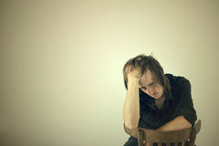 Portrait of the thoughtful guy sitting on a chair Royalty Free Stock Photos