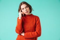 Portrait of a thoughtful young woman. Dressed in sweater looking away at copy space isolated over blue background Royalty Free Stock Photo