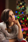 Portrait of thoughtful young woman in front of christmas lights Stock Photo